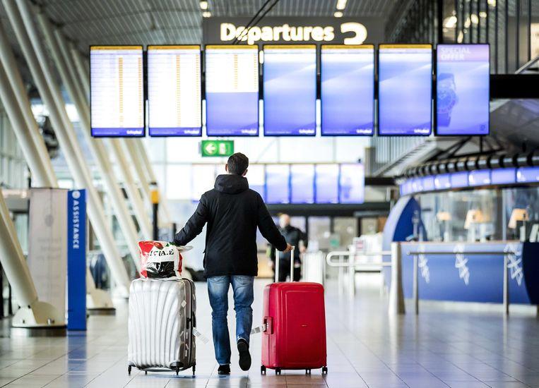 Een reiziger op Schiphol bekijkt de uitgaande vluchten. Beeld ANP
