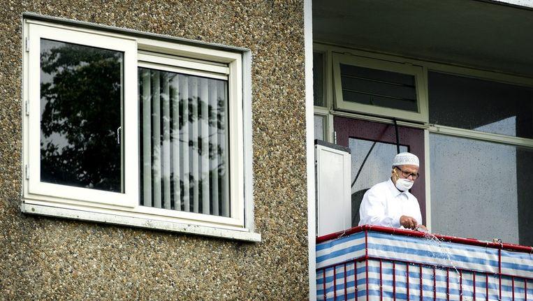 Een bewoner van de met asbest besmette flat aan de Marco Pololaan in de Utrechtse wijk Kanaleneiland spuit zijn balkon schoon na terugkomst. Beeld anp
