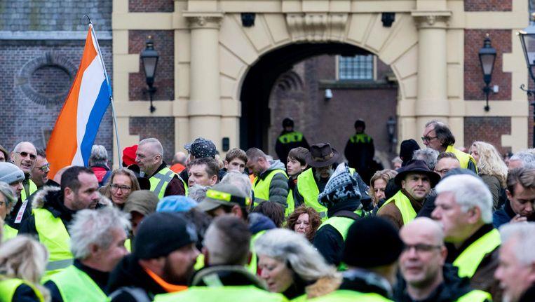 De gele hesjes kwamen zaterdag bijeen op het Binnenhof in Den Haag. Op de achtergrond voert één van hen de omstreden Prinsenvlag. Beeld anp