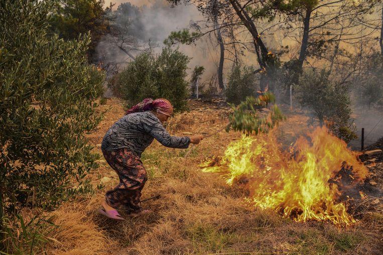 Een vrouw probeert het verspreidende vuur te doven in het dorp Kacarlar.  Beeld AP