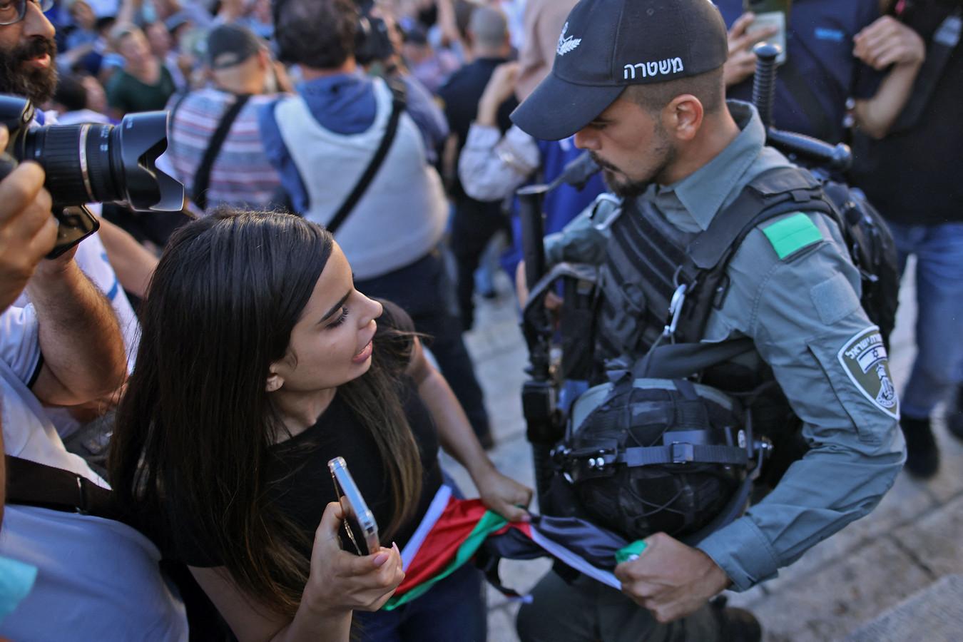 Een Israëlische agent probeert een Palestijnse vlag van een vrouw af te nemen tijdens de vlaggenmars.