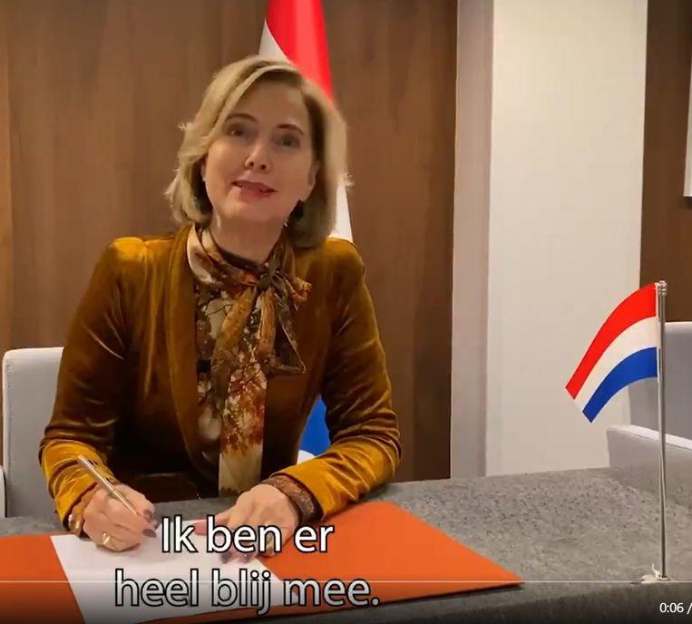 Minister met nationale vlaggen. Beeld Ministerie voor Asfaltzaken