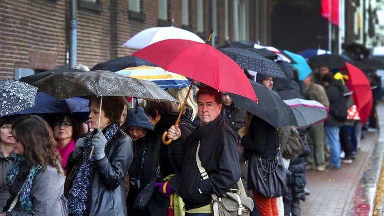 Bezoekers met paraplu's in de rij voor museum De Hermitage in Amsterdam. Beeld anp