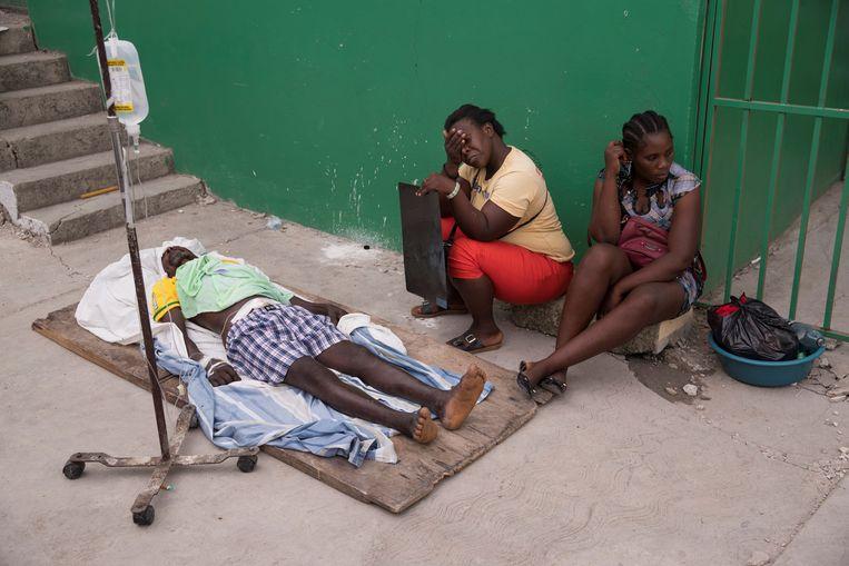 Een slachtoffer wordt behandeld buiten het ziekenhuis in Les Cayes, Haïti. Beeld EPA