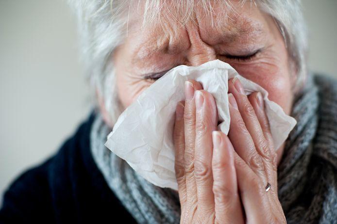 Een vrouw snuit haar neus.