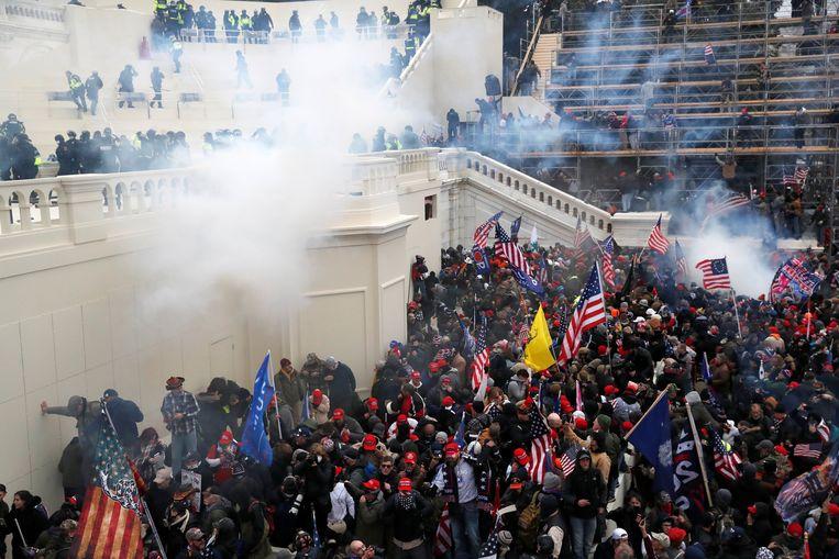 Wolken traangas hangen boven de massa, terwijl die het Capitool bestormt. Beeld REUTERS