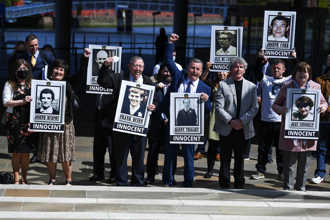 Nabestaanden met foto's van de slachtoffers in Belfast