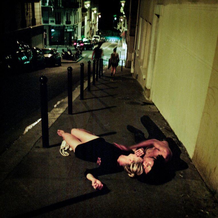 Frankrijk, Parijs, 01 september 2016, een jong stel ligt op een warme zomernacht onder invloed van alcohol of drugs op het trottoir te knuffelen. Beeld null