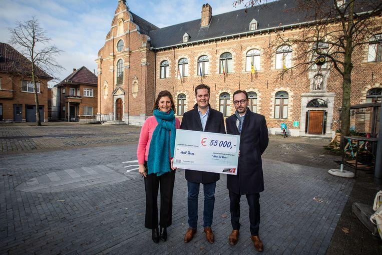 Burgemeester Liesbeth Van der Auwera (links) ontvangt van Tom Vandeput (midden) de cheque van 55.000 euro. Bart Lodewyckx van UNIZO kijkt tevreden toe.