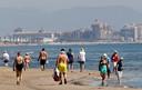 Zonnebaders op het strand van Valencia.