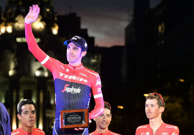 Trek-Segafredo's Spanish cyclist Alberto Contador waves on the podium as he holds a farewell plaque from La Vuelta organization after the 21th and last stage of the 72nd edition of
