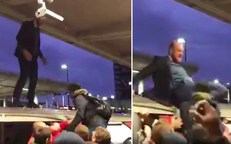 De boze pendelaars sleuren een klimaatbetoger van het dak van hun metro.