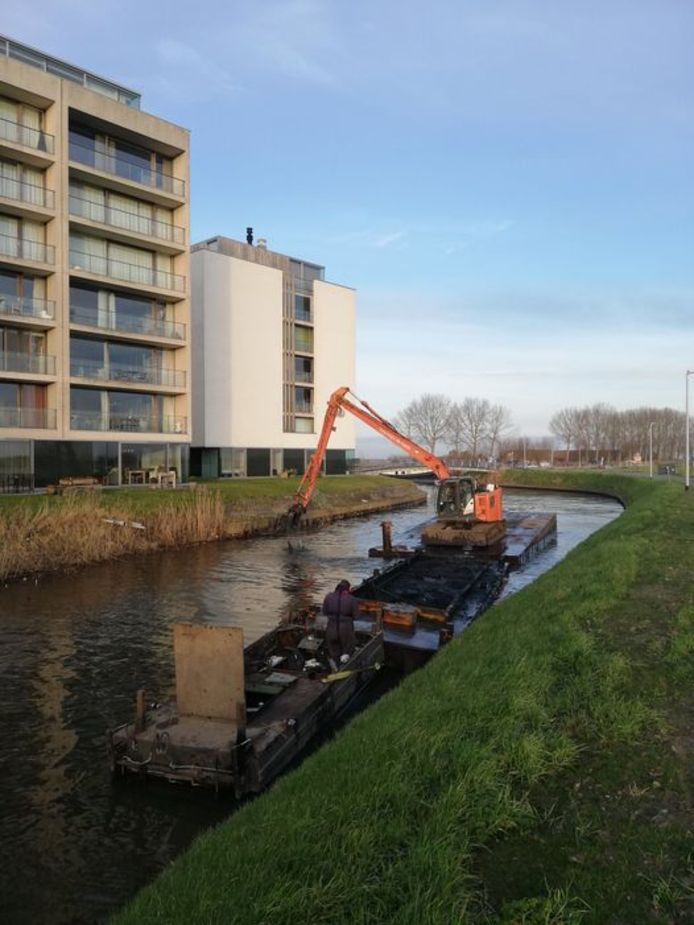 Een kraan ruimt het slib in de Handzamevaart in Diksmuide, van op een ponton. Het moet wateroverlast vermijden en de ecologische toestand verbeteren.