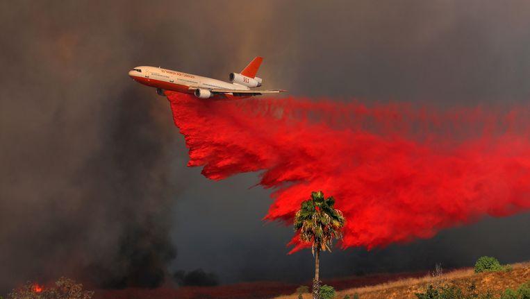 Een blusvliegtuig vliegt boven Orange in Californië. Beeld reuters
