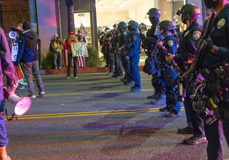 Aanhangers van Trump tegenover politie in Los Angeles, Californië. Beeld EPA