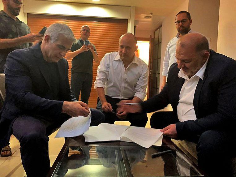 Met een pennenstreek zegt Mansour Abbas (r), de leider van de Verenigde Arabische Lijst, zijn steun toe aan een regering onder Naftali Bennett (m) en Yair Lapid (l). Het is de eerste keer dat een Arabische partij meedoet aan een Israëlische regering.  Beeld AFP