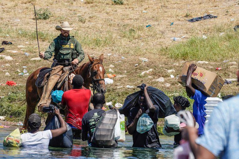 Een grensagent gebruikt zijn teugels om Haïtiaanse migranten tegen te houden. Beeld AFP