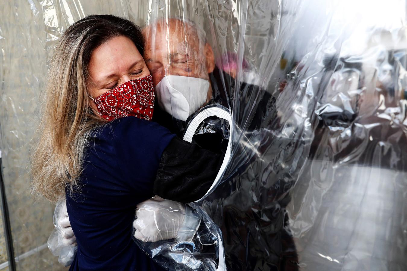 Maria Paula Moraes knuffelt haar 82-jarige vader. De twee zijn vanwege het coronavirus gescheiden door een 'knuffelgordijn' in Sao Paulo, Brazilië.
