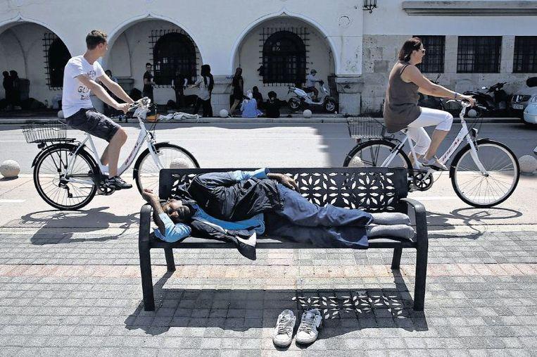 Westerse toeristen fietsen door de straten van Kos, waar bootvluchtelingen rondhangen in afwachting van hun tijdelijke verblijfsvergunning. Beeld reuters