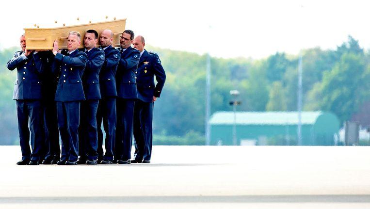 2 mei 2015: een van de laatste kisten met stoffelijke resten van slachtoffers van rampvlucht MH17 wordt naar een rouwwagen gedragen na aankomst uit Charkov op vliegbasis Eindhoven. Beeld null