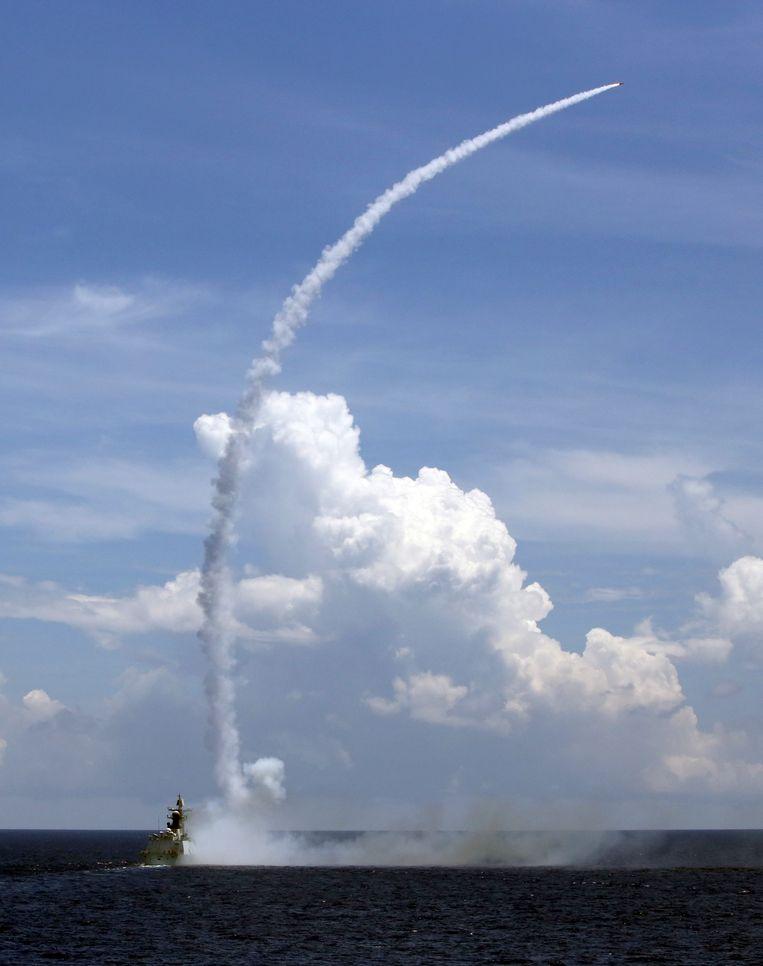 Een Chinees militair fregat lanceert een raket nabij Hainan. Beeld AP
