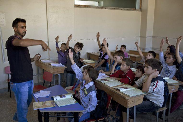 Syrische kinderen krijgen les in een schooltje in het Saif Al-Dawla district in Aleppo. Beeld EPA