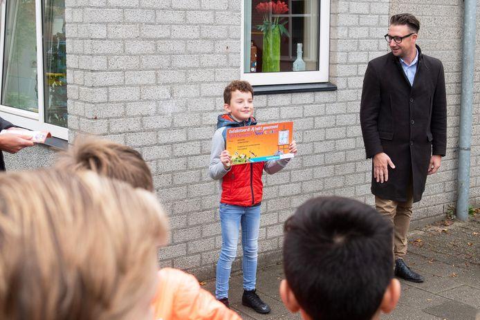 Het eerste boekje van Sjors Sportief werd uitgereikt door wethouder Mike Hofkens (R) aan de tekenwinnaar Seth Voermans.