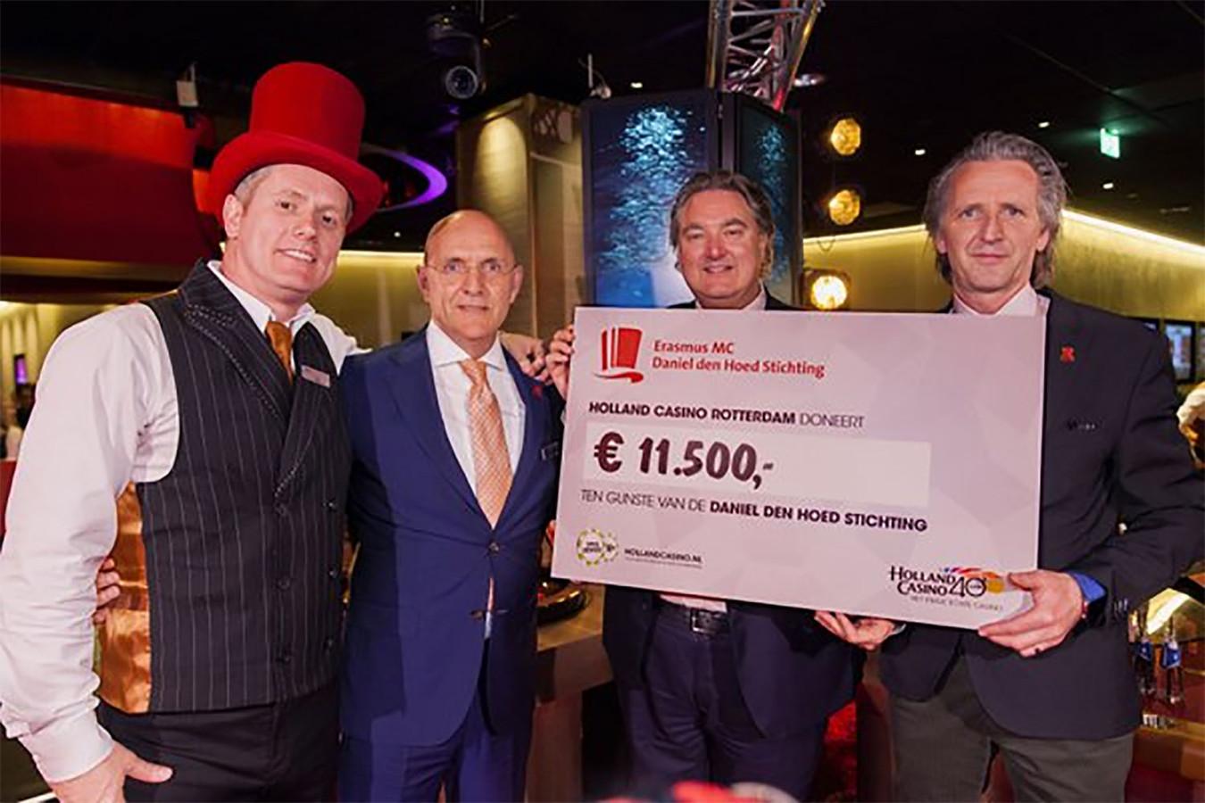 Directeur van Holland Casino Erwin van Lambaart en de Rotterdamse casinomanager Peter Voolstra overhandigen een cheque aan professor Leendert Looijenga van de Daniel den Hoed Stichting.