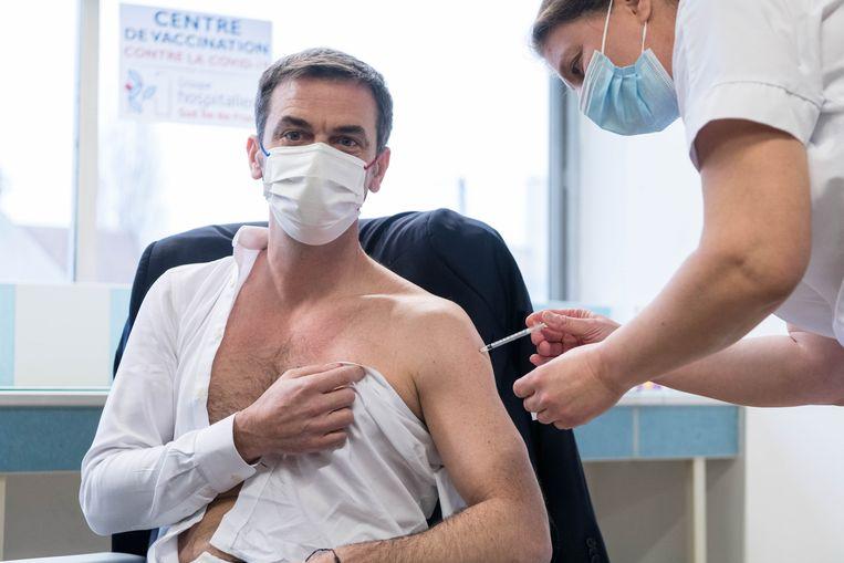De Franse minister van Volksgezondheid Olivier Veran krijgt het AstraZeneca-vaccin toegediend. In Zuid-Afrika is de toediening van dat vaccin voorlopig stopgezet. Beeld Photo News