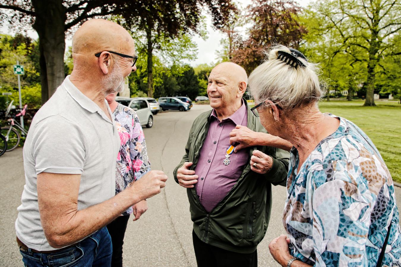 Joop Bloemendal toont zijn zojuist ontvangen lintje aan zijn familie.