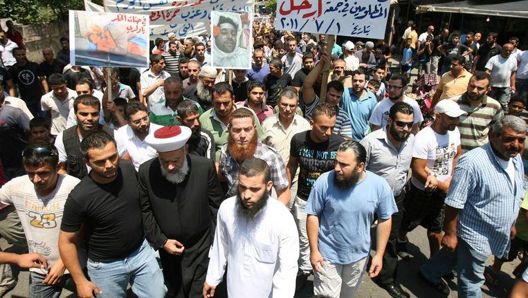 Syrische demonstranten dragen spandoeken meee en afbeeldingen van vermoorde geliefden. Beeld REUTERS