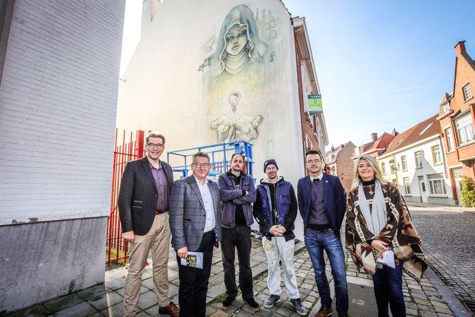 Schepen Franky Demon, burgemeester Dirk De fauw, kunstenaars Sammy Slabbinck en JamzJamezonin en schepenen Mathijs Goderis en Mercedes Van Volcem aan de mural in de Sint-Clarastraat.