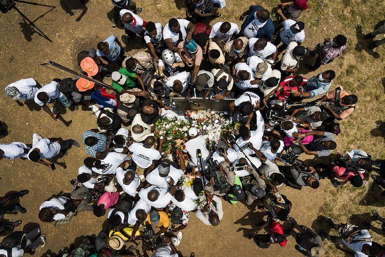 Omringd door de pers maken aanhangers van de vermoorde Haïtiaanse president Jovenel Moïse woensdag 14 juli bij het presidentiële paleis in de hoofdstad Port-au-Prince een gedenkplaats met bloemen, sigaren en kaarsen. Beeld Matias Delacroix /AP