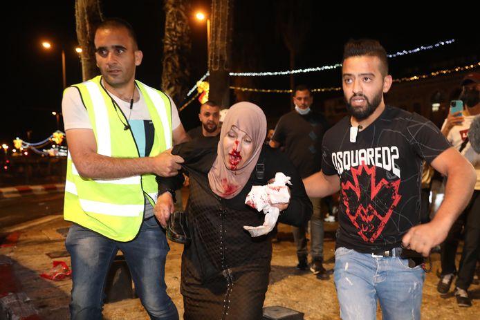 Twee mannen helpen een Palestijnse vrouw die gewond is geraakt bij een betoging tegen de uitzetting van zes Palestijnse gezinnen in Jeruzalem.