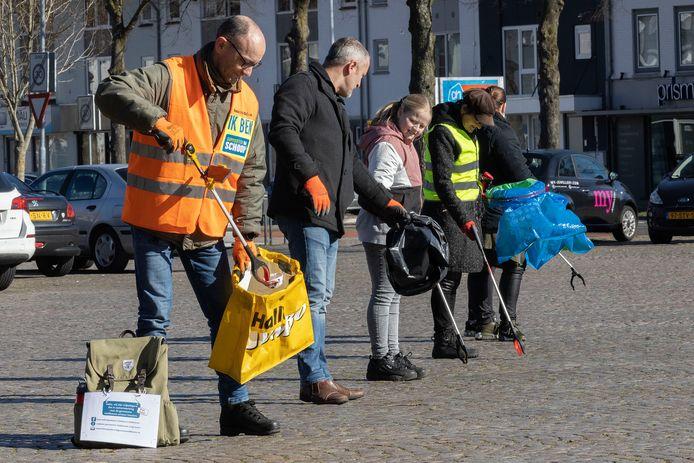 Harrie Verberne (l)  ruimt samen met andere vrijwilligers zwerfvuil op in Veldhoven.