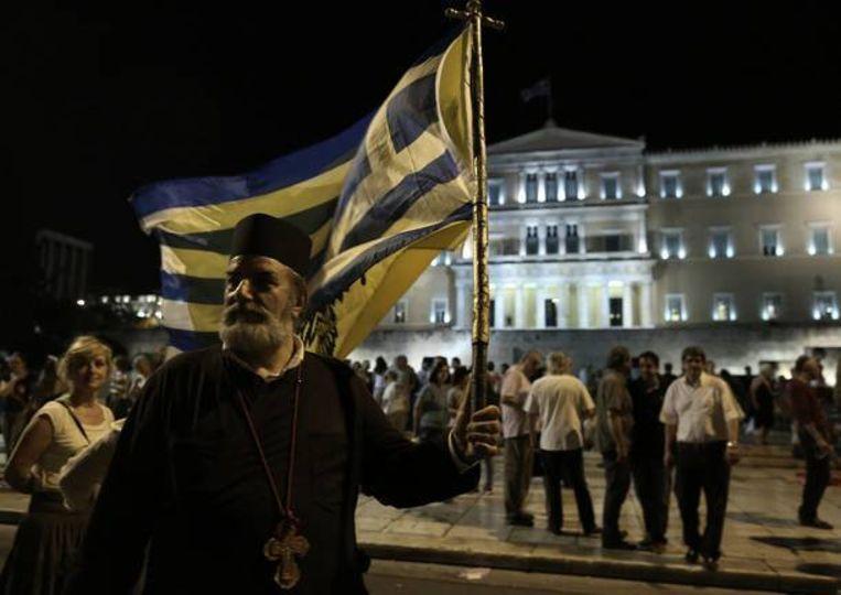Een priester van de Griekse orthodoxe kerk bij een demonstratie tegen bezuinigingen voor het Griekse parlement. Beeld EPA