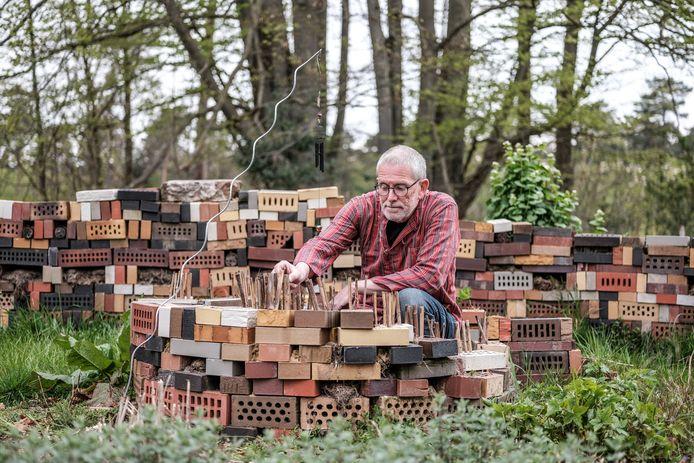 Jaap Molenaar bij een muurtje voor insecten van ouwe klinkers voor diverse soorten insecten en met houten varianten voor de rosse metselbij.