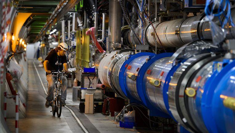 Een arbeider inspecteert per fiets een tunnel van de Large Hadron Collider in het CERN in Zwitserland. Beeld AFP