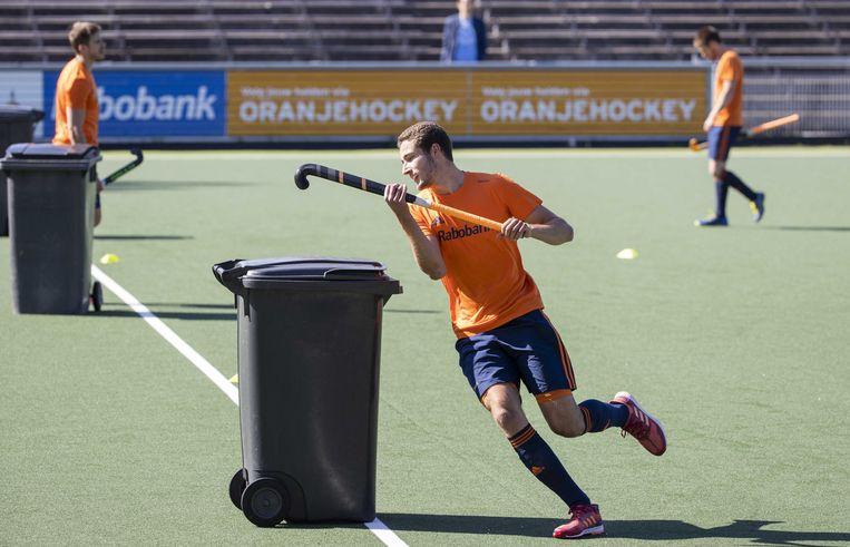 Jonas de Geus rondt een kliko. De vuilnisbak fungeert als verdediger nu afstand bewaren de opdracht is op de eerste training van de nationale hockeyploeg.   Beeld Koen Suyk/ANP