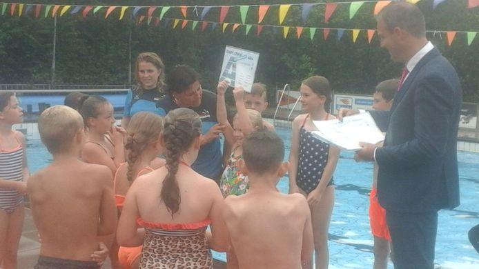 Wethouder Johan Aalberts reikt eerste diploma's uit van het geprivatiseerde zwembad in Arnemuiden.
