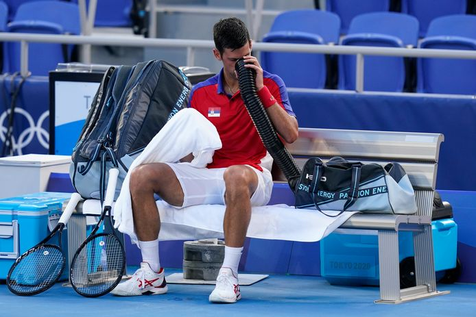 Novak Djokovic blaast zichzelf wat frisse lucht toe tijdens zijn partij met Alejandro Davidovich Fokina.