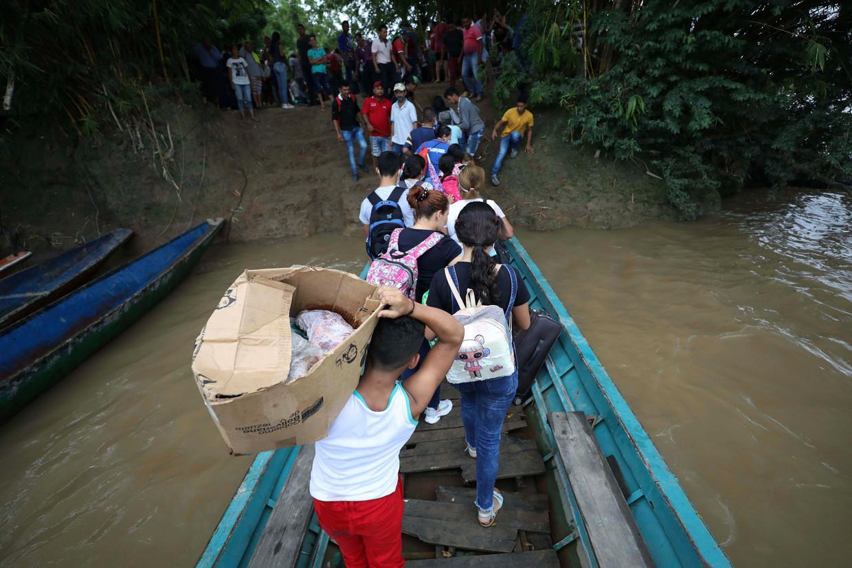 Gevluchte Venezolanen stappen van het bootje waarmee ze de Aruaca-rivier zijn overgestoken naar Colombia, eind maart. Beeld Fernando Vergara / AP