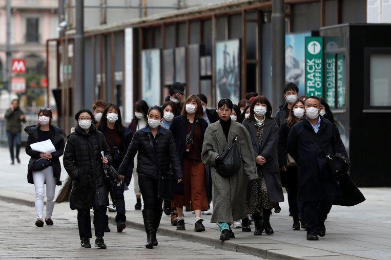 Toeristen met mondmaskers in Milaan. Hier zie je de maskertjes nog niet opduiken. 'Het is puur om in de kast te leggen, als een soort geruststelling.' Beeld REUTERS