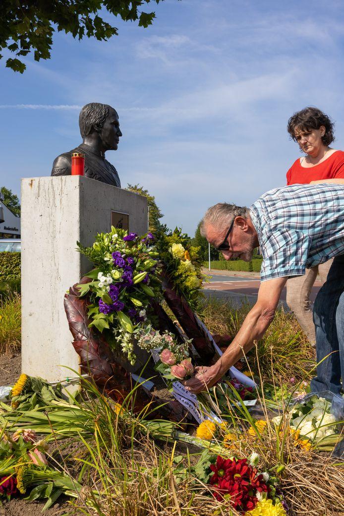 Arnoud en Carola Verlouw uit Ammerzoden leggen bloemen neer bij het borstbeeld van de oud-motorcoureur Boet van Dulmen.