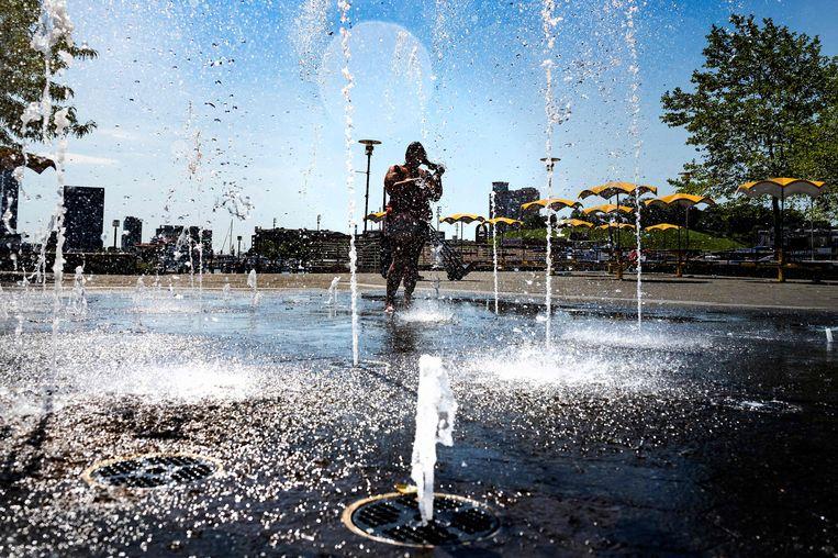 Een vrouw wast haar haren in een fontein in Baltimore, Maryland. Daar is een hittegolf. Beeld AFP