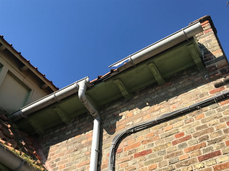Losse dakpannen en dakgoten geven de school geen fraaie aanblik.