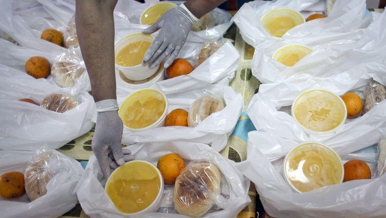 Een vrijwilliger bereidt maaltijden voor de armen in de Portugese stad Setubal. Beeld AFP