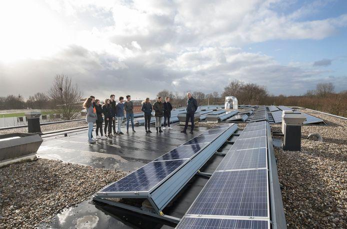 Natuurkundeleraar Michiel van Duin vertelt op het dak van het Pallas Athene College aan een groepje leerlingen uit 4 vwo hoe zonnepanelen werken.