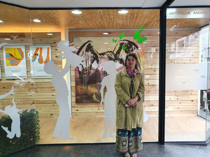 Jonge kunstenares Denisa Teglas (22) voor de vitrine van BioSpace, waar kunst voor voorbijgangers wordt tentoongesteld.