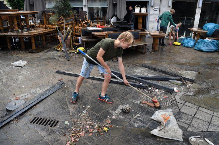 Kinderen helpen mee opruimen in Valkenburg. Beeld Marcel van den Bergh / de Volkskrant
